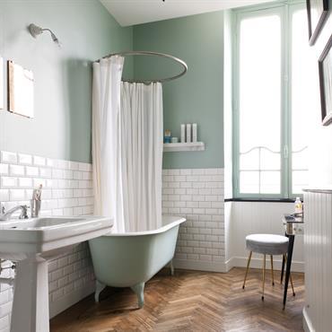 Salle de bain au mobilier de style ancien. Briques métro en soubassement