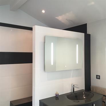 Salle de bain monochrome avec miroir éclairage intégré
