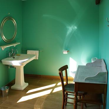 Coin lavabo et coiffeuse ancienne dans la salle de bain turquoise