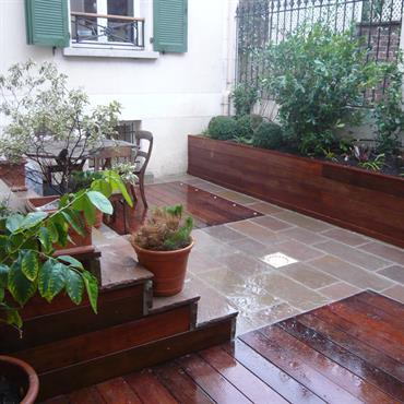 La terrasse est réaménagée avec deux matériaux : l'ipé et le grès naturel. Ce traitement permet d'agrandir l'espace visuellement et de délimiter deux espaces au sol. La grande jardinière est ...