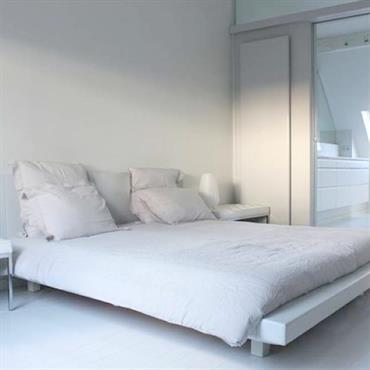Chambre avec salle de bain  lit avec linge de maison en lin blanc grisé. Parquet peint et laqué blanc. Avec tables de nuits de designer.