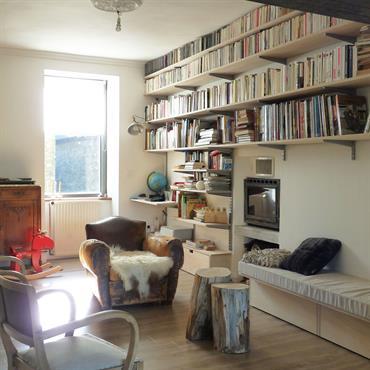 Ambiance cosy grâce au fauteuil club et à la cheminée à bois