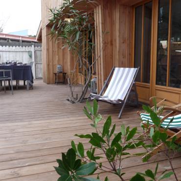 Terrasse en bois avec chaises longues et coin repas
