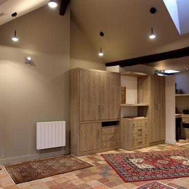 Bibliothèques et placards en bois, carrelage terre cuite, tapis de style ancien.