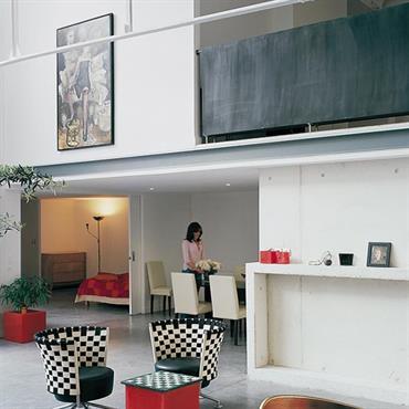Salon avec mur en béton brut. Fauteuil en cuir avec des motifs en damier noir et blanc