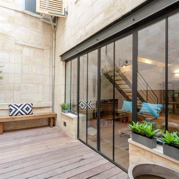 Terrasse de maison contemporaine avec grande baie vitrée industrielle - Coin salon extérieur
