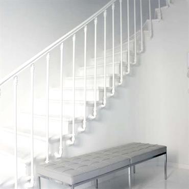 Cage d'escalier toute repeinte en blanc avec à l'entrée une banquette d'accueil en cuir blanc capitonnée du designer StarcK.