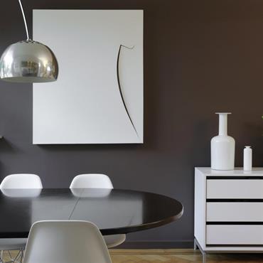 Salle à manger contemporaine en clair-obscur. Table ovale en bois noir verni