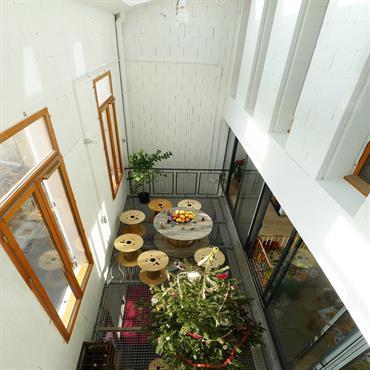 Serre bioclimatique avec terrasse intérieure en caillebotis métallique.