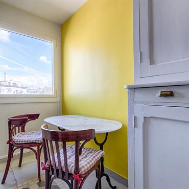 Coin repas dans la cuisine, avec un mur jaune pour la luminosité de la pièce