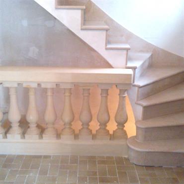 Ensemble classique pour cet escalier tournant en pierre assorti d'une balustrade.