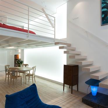 Le mur de lumière souligne la hauteur du loft dont les deux niveaux sont reliés par  l'escalier suspendu en chêne blanchi.