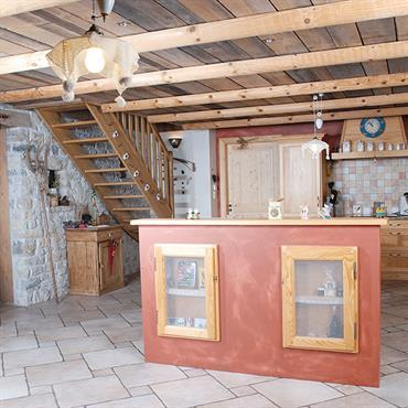 Cuisine de style vintage avec murs en pierres, poutres apparentes et plancher, îlot central ocre