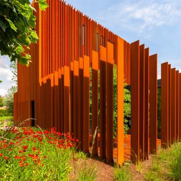 La façade en acier Corten de la maison se prolonge en palissade entourant le jardin