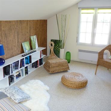 Espace lecture avec une bibliothèque et des fauteuils