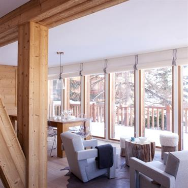 Dans une ambiance bois, ce salon arbore un mélange de fauteuils contemporains et de clins d'oeil déco montagne.