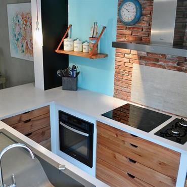 Cuisine moderne ouverte. Briques apparentes et tiroirs en bois côtoie des surfaces lisses, blanches, bleues et grises
