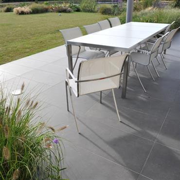 La terrasse contemporaine offre des lignes simples et neutres, créant une articulation subtile avec le jardin.