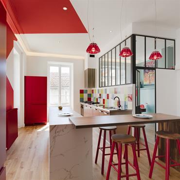 Géométrie murale et crédence multicolore se marie pour apporter de la couleur à cette cuisine. Le plan de travail en marbre et bois est très tendance en ce moment