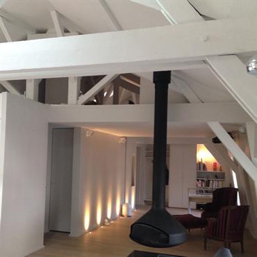 Vue sur l'entrée, cheminée suspendue au centre de la pièce à vivre