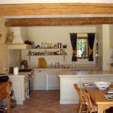 Cuisine avec poutres apparentes en bois naturel. Plafond blanc. Murs crèmes. Meubles de cuisine blancs cassé style ancien
