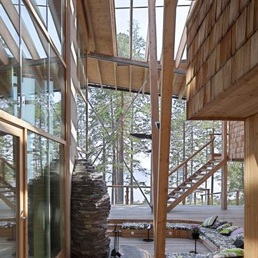 Le salon et la cheminée sont incrustés dans la terrasse flottant au dessus des lichens du sol de la forêt.