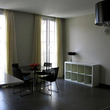Salle à manger avec table ronde noire et chaises noires