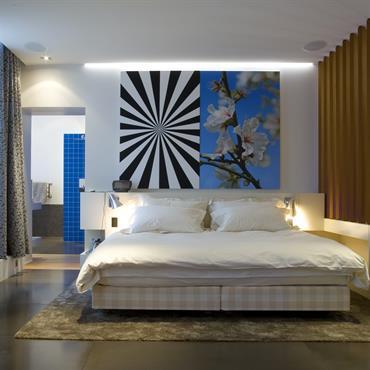Suite parentale avec faux plafond équippé d'un système audio. Oeuvre d'art monumentale en tête de lit.