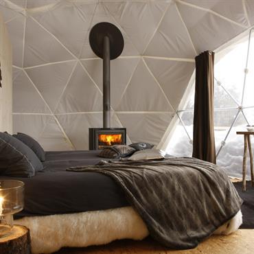 Chambre cocooning aux tons sombres dans une maison bulle