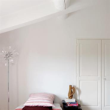 L'ambiance épurée dans cette chambre aux murs blancs et aux poutres apparentes peintes fonctionne aussi bien pour une chambre d'ado que pour une chambre d'amis.