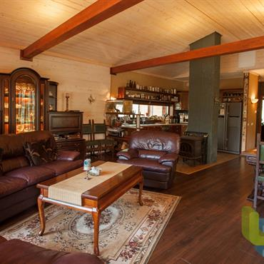 Pièce à vivre au mobilier classique, architecture bois. Meubles d'époque en bois, salon en cuir