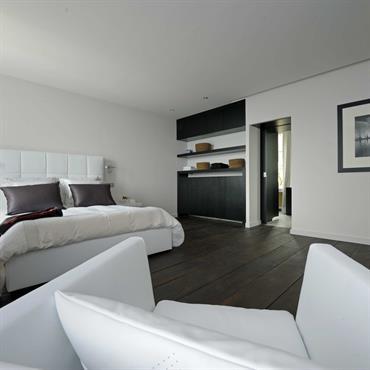 Chambre avec parquet sombre et mobiliers blancs. tête de lit en cuir blanc