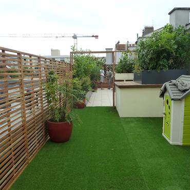 Terrasse avec gazon synthétique et palissade de bois