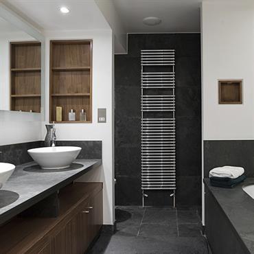 Sobre et contemporaine, cette salle de bain associe le côté minéral de la pierre grise et le bois du meuble sous vasque et de l'habillage des niches murales.