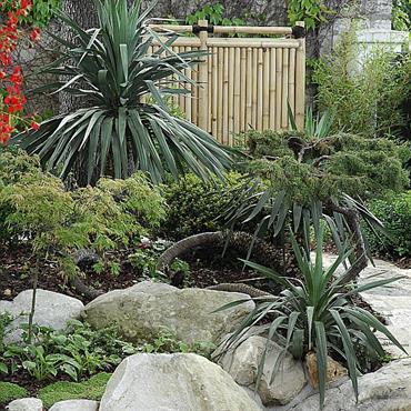 Massifs de plantes et rochers de Fontainebleau ont été aménagés et les murs ont été décorés de palissades en bambous et osier.