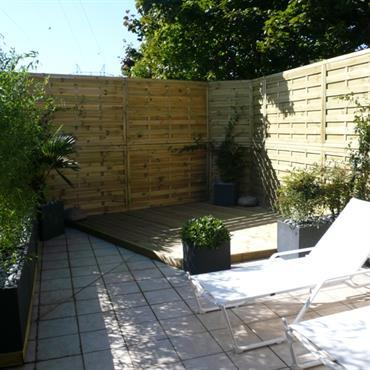Terrasse paysagée fermée par palissade en bois. Plantations de bambous dans des jardinières modernes en métal.
