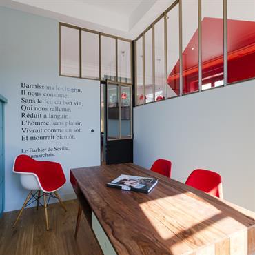 Bureau avec verrière industrielle, mobilier coloré, et stickers citation mural