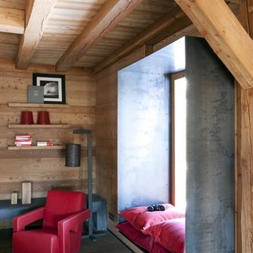 Un coin repos avec du bois brut pour l'esprit zen, de l'acier pour le mélange de matériaux nobles et du rouge pour le clin d'oeil tendance moderne.