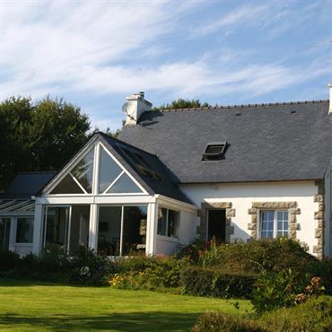 Véranda avec une toiture en ardoise et des baies vitrées