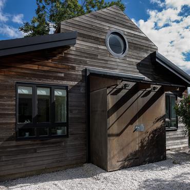 La terrasse en graviers de quartz blanc contraste et illumine le bardage en red cédar de la maison.