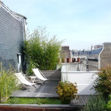 Terrasse de ville paysagée sur les toits avec plancher en bois, gazon et jardinières. Un bel endroit pour profiter de la vue sur la ville