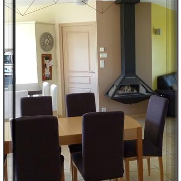 Salle à manger ouverte sur la cuisine. La modernité du poêle et de la suspension viennent secouer un intérieur relativement classique.