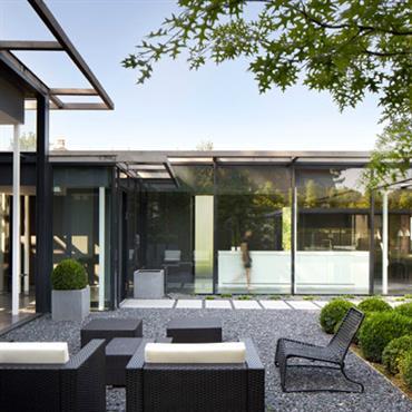 Terrasse en gravier pour une maison avec des façades en verre