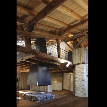 Pièce principale avec cheminée centrale finition acier noir, sole foyère en pierres de pays, habillage vieux bois, aciers doux