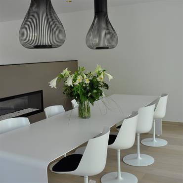 Salle à manger au design épuré. Table en plaque de polycarbonate moulée, parquet en bois clair.