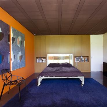 Une chambre haute en couleur. Des couleurs complémentaires bleu et orange Sol et plafond ayant la même couleur prune qui donne l'illusion qu'ils sont plus rapprochés,