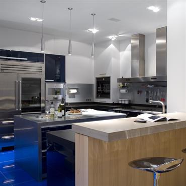Dans la cuisine de niveau professionnel, mobilier et équipements haut de gamme. Bar et îlot. Quartz bleuté au sol.