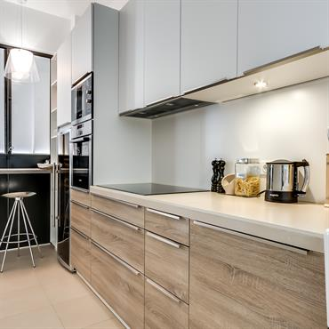 La cuisine contemporaine avec meubles bois et blancs se ferme selon les besoins grâce à une verrière escamotable.
