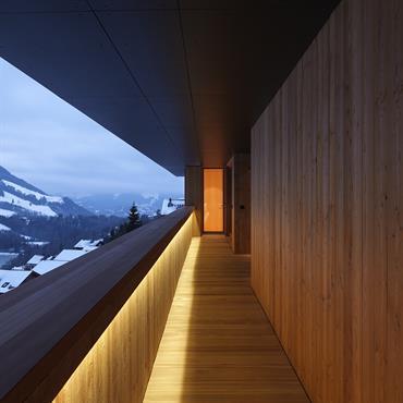 Long couloir cadrant sur le panorama. Revêtement en bois en harmonie avec la nature environnante.