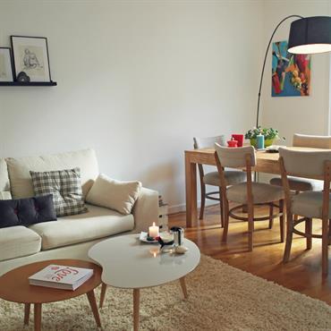 Salon avec canapé blanc. Salle à manger avec table en bois naturel. Chaises en bois avec assise et dossier de tissus blanc. Table basse design et lampadaire design